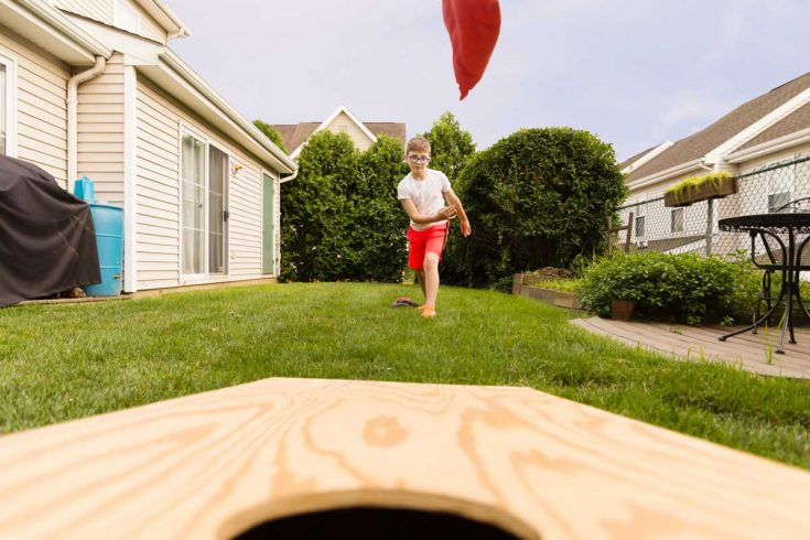 Boy playing cornhole, bean bag tossed in the air.